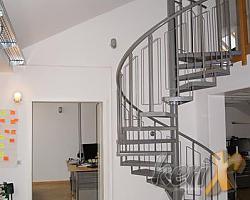 Schody kręcone, których stopnie wykonane są z blachy ryflowanej, balustrada stalowa z poręczą giętą stalową. Całość malowana proszkowo. Miejsce montażu : Berlin , Niemcy