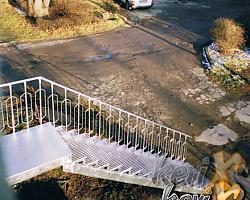 """Schody proste z podestem, balustrada """"VIP"""". Stopnie- krata pomostowa, podest- blacha ryflowana. Wykonanie- Frankfurt n. Menem, Niemcy."""